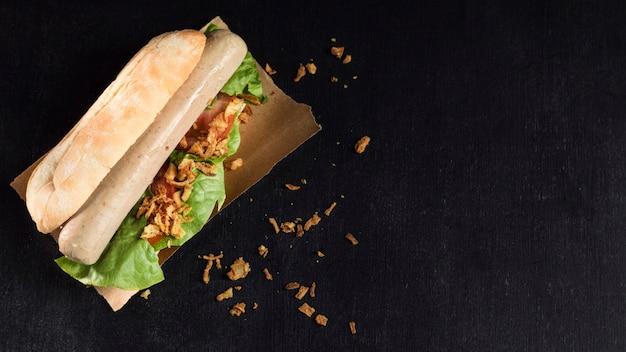 Delicioso hot dog de comida rápida sobre fondo de espacio de copia de papel para hornear