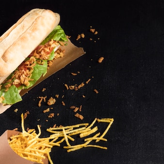 Delicioso hot dog de comida rápida sobre papel de hornear plano
