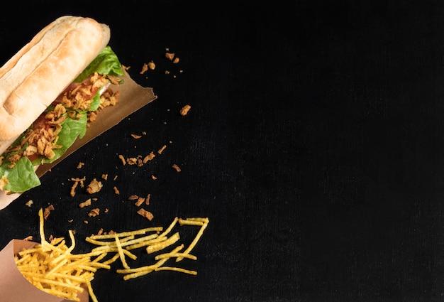 Delicioso hot dog de comida rápida sobre papel para hornear con queso