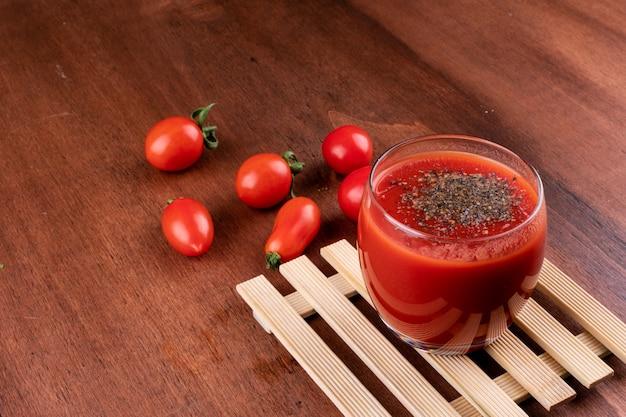 Delicioso jugo de tomate rojo en vaso con pimienta negra en la mesa de madera