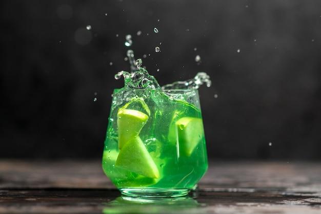 Delicioso jugo en un vaso con limones de manzana sobre fondo oscuro