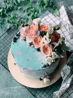 Delicioso y jugoso pastel casero decorado con crema azul y flores frescas sobre fondo azul.