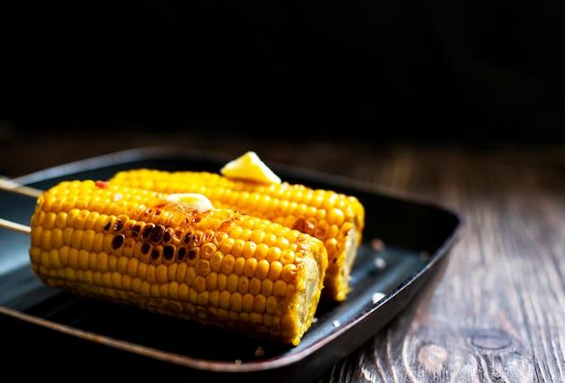 Delicioso maíz a la parrilla con mantequilla y sal en una sartén a la parrilla sobre una madera rústica
