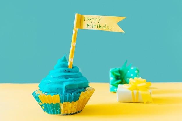 Delicioso muffin con bandera de feliz cumpleaños cerca de regalo en superficie amarilla