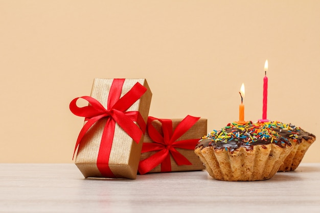 Delicioso muffin de cumpleaños con glaseado de chocolate y caramelo, decorado con velas festivas encendidas y cajas de regalo con cintas rojas sobre fondo beige. feliz cumpleaños concepto mínimo.