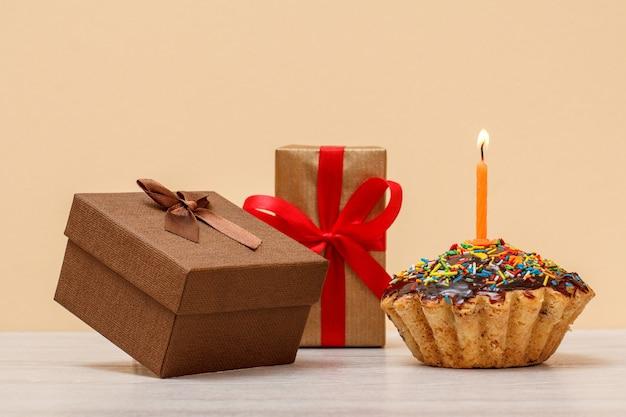 Delicioso muffin de cumpleaños con glaseado de chocolate y caramelo, decorado con velas festivas encendidas y cajas de regalo sobre fondo beige. feliz cumpleaños concepto mínimo.