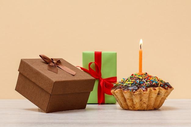 Delicioso muffin de cumpleaños con glaseado de chocolate y caramelo, decorado con velas festivas encendidas y cajas de regalo sobre fondo de color beige. feliz cumpleaños concepto mínimo.