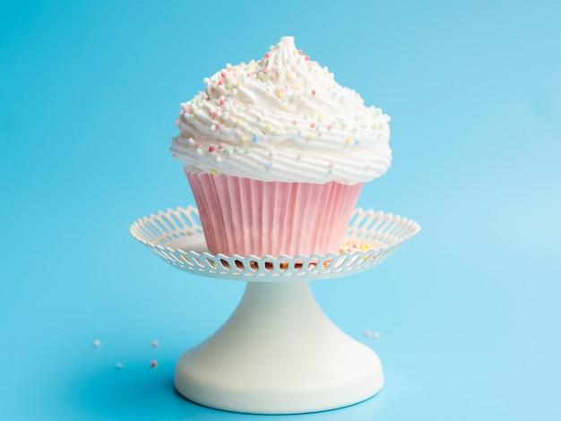 Delicioso muffin de cumpleaños sobre fondo azul.