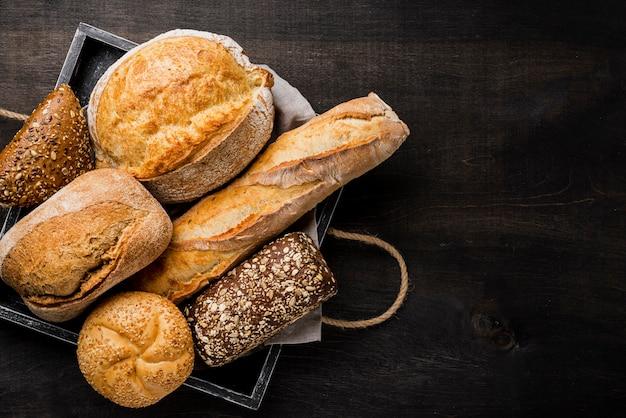 Delicioso pan blanco y de grano entero en canasta de madera