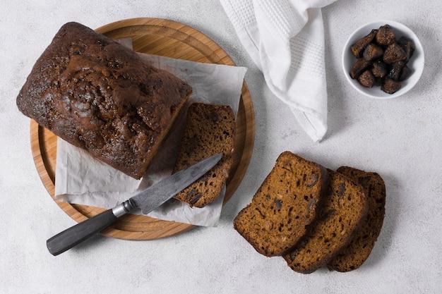 Delicioso pan dulce sobre tabla de madera con cuchillo