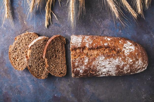 Delicioso pan rebanado en la superficie oscura. vista superior