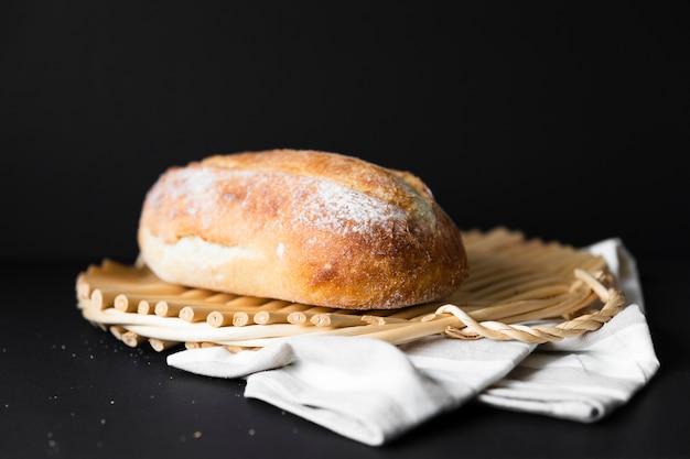 Delicioso pan de tamaño entero sobre tela y fondo negro