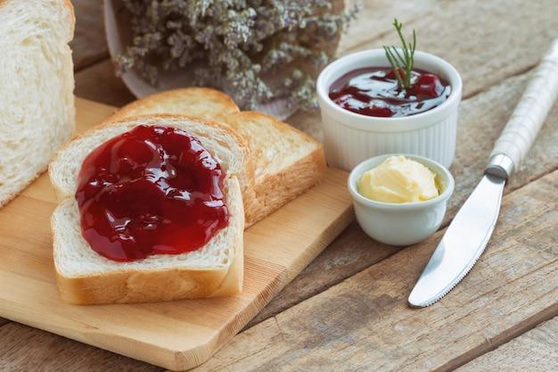Delicioso pan tostado servido con mantequilla y untado con mermelada de fresa para el desayuno.