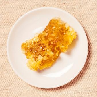 Delicioso panal en plato blanco sobre yute con textura
