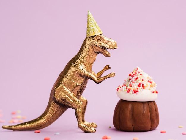 Delicioso panecillo y dinosaurio con gorro de cumpleaños