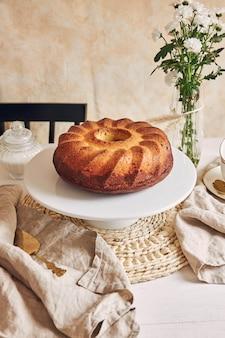 Delicioso pastel de anillo puesto en un plato blanco y una flor blanca cerca