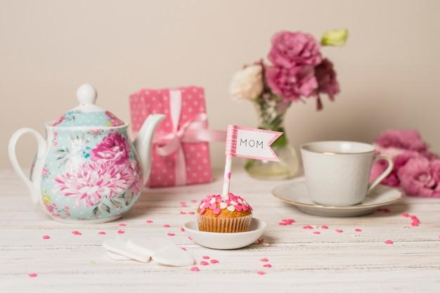Delicioso pastel con bandera decorativa con título de mamá cerca de tetera, flores y taza