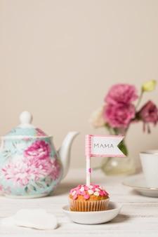 Delicioso pastel con bandera decorativa con título de mamá cerca de tetera y flores