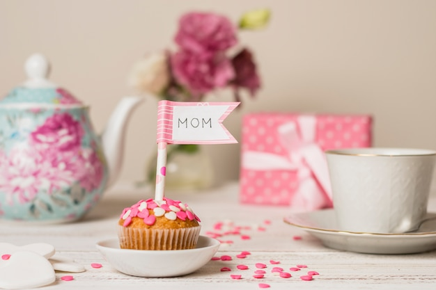 Delicioso pastel con bandera decorativa con título de mamá cerca de tetera y taza