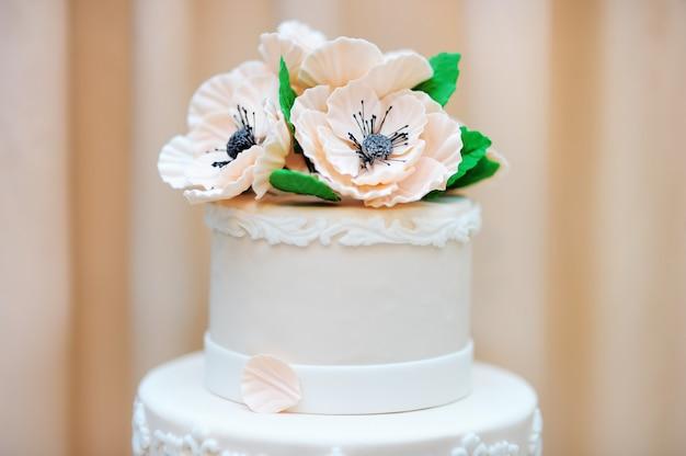 Delicioso pastel de bodas o cumpleaños blanco decorado con flores.
