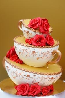 Delicioso pastel de bodas original decorado con flores rojas.