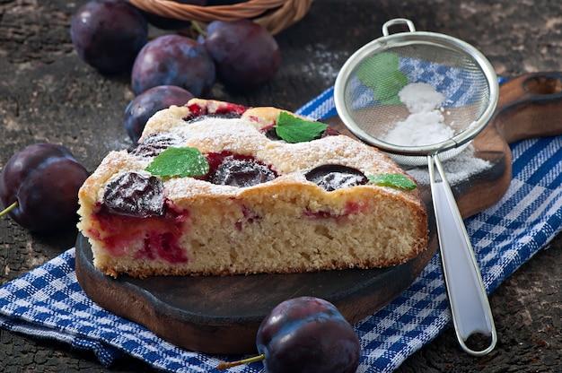 Delicioso pastel casero con ciruelas en madera