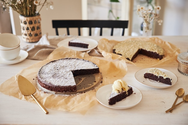Delicioso pastel de chocolate con crema sobre una mesa blanca presentado con detalles estéticos