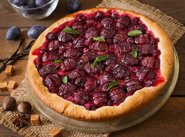 Delicioso pastel con ciruelas frescas y frambuesas