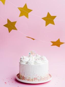 Delicioso pastel de cumpleaños y estrellas doradas