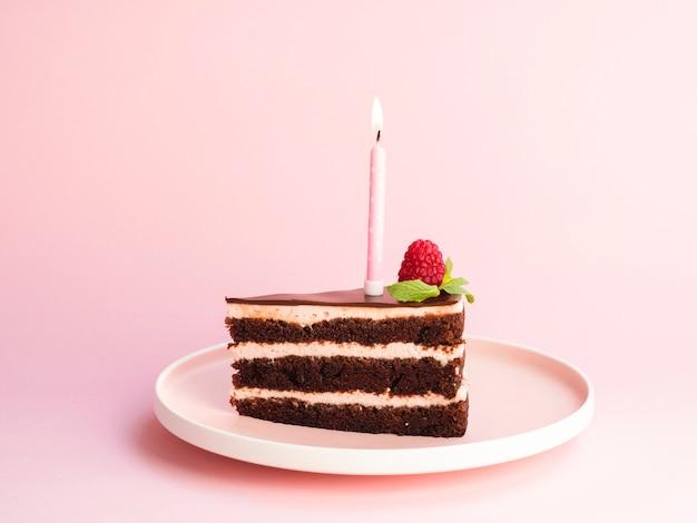 Delicioso pastel de cumpleaños sobre fondo rosa