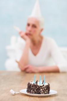 Delicioso pastel frente a la mujer desenfocada