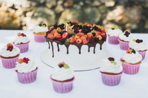 Delicioso pastel de frutas con cupcakes para un feliz cumpleaños