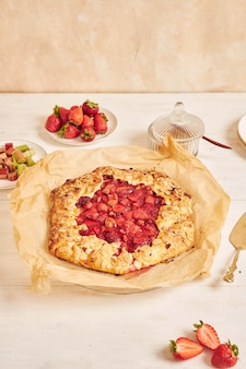 Delicioso pastel de gallate de fresas de ruibarbo con ingredientes sobre una mesa blanca