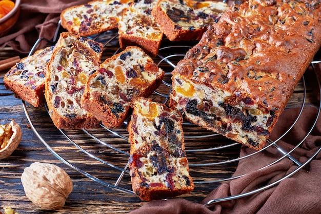 Delicioso pastel grueso de frutos secos en un soporte de pastel de alambre con tela marrón, palitos de canela, albaricoques secos y frutos de dátil en una mesa de madera rústica, vista desde arriba, primer plano