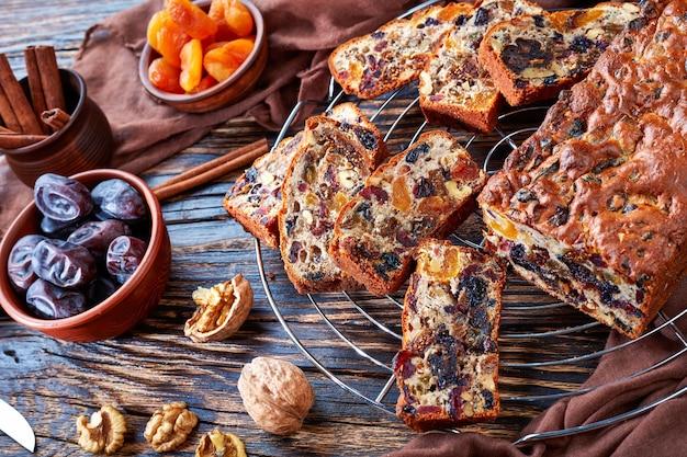 Delicioso pastel de hogaza de frutos secos en un soporte de alambre con tela marrón, palitos de canela, orejones y frutos de dátil en una mesa de madera rústica, vista desde arriba