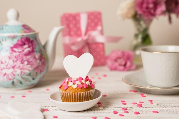 Delicioso pastel junto a la tetera, presente y taza.