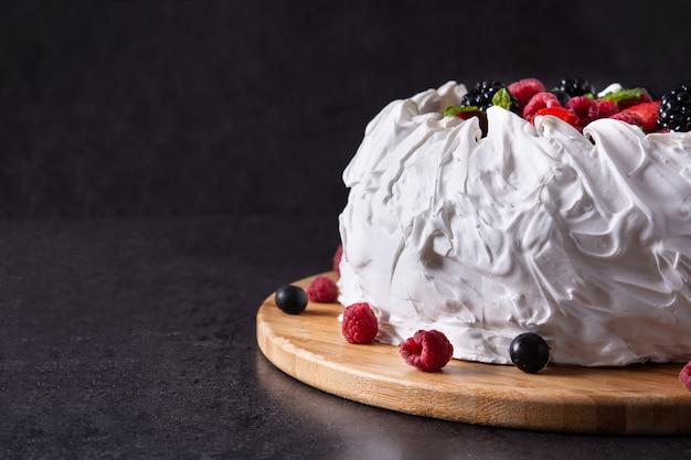Delicioso pastel de pavlova con merengue y bayas frescas sobre fondo negro