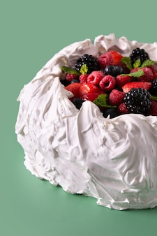 Delicioso pastel de pavlova con merengue y bayas frescas sobre fondo verde
