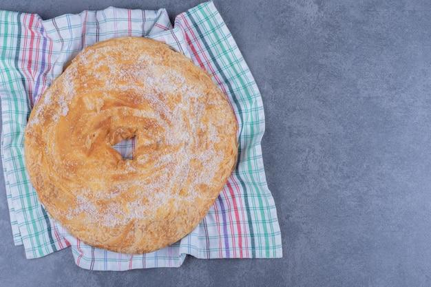 Un delicioso pastel redondo con azúcar en polvo sobre un mantel