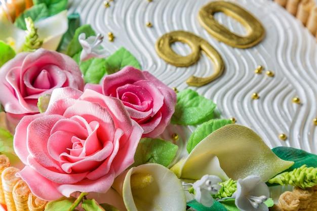 Delicioso pastel con rosas, lirios, hojas y figuras de 90 años en la mesa de madera azul claro de cerca