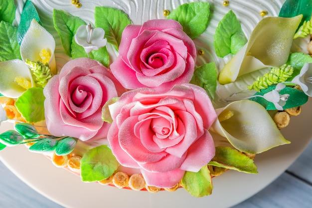 Delicioso pastel con rosas, lirios y hojas en la mesa de madera azul claro de cerca