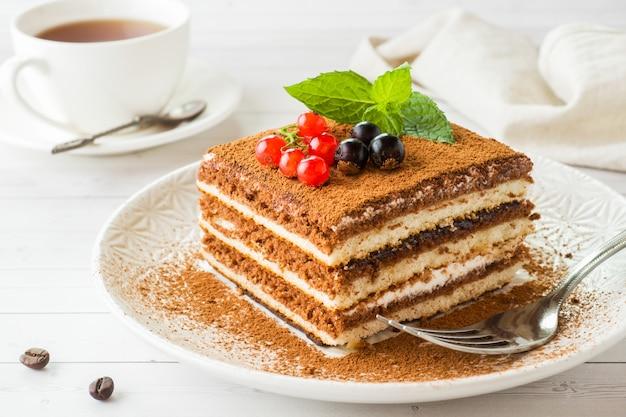 Delicioso pastel de tiramisú con bayas frescas y menta en un plato
