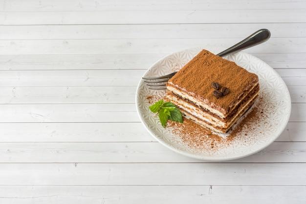 Delicioso pastel de tiramisú con granos de café y menta fresca en un pl
