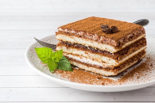 Delicioso pastel de tiramisú con granos de café y menta fresca.