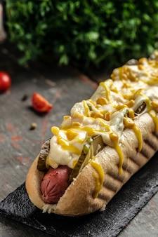 Delicioso perrito caliente fresco con salchicha casera envuelto perritos calientes con queso y maíz. imagen vertical. vista superior. lugar para el texto