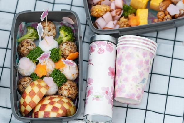 Delicioso picnic con flores de cerezo.