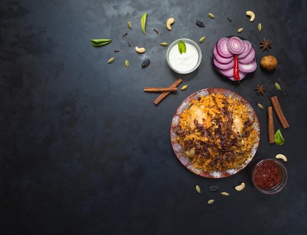 Delicioso pollo picante biryani en un tazón blanco sobre fondo negro, comida india o paquistaní.