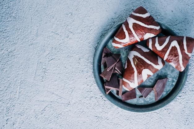 Delicioso postre casero de chocolate blanco y negro relleno de crema. postre en forma de triángulo en la mesa de madera