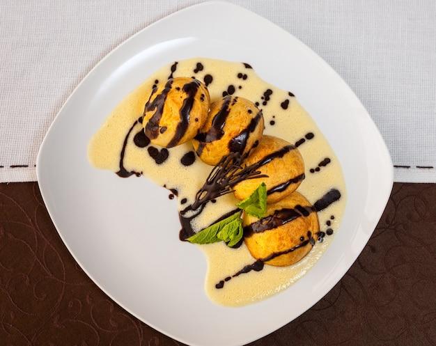 Delicioso postre con chocolate, salsa dulce, tartas y menta en una placa blanca.