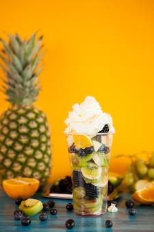 Delicioso postre de verano de ensalada de frutas con crema batida en la parte superior. refresco tropical dulce
